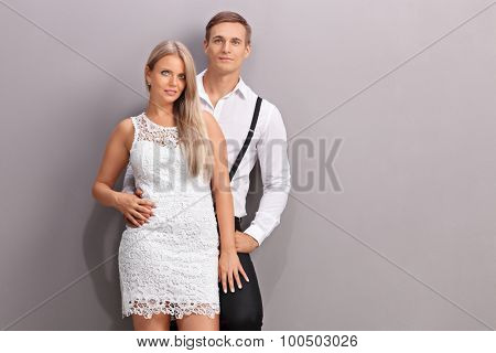 Fashionable young couple in stylish clothes posing together in front of a gray wall