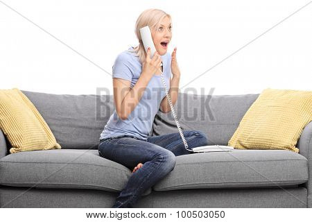 Pleasantly surprised girl talking on the telephone seated on a gray sofa isolated on white background