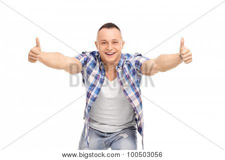 Full length portrait of a joyful guy with an attitude, giving thumbs up, smiling and looking at the camera isolated on white background
