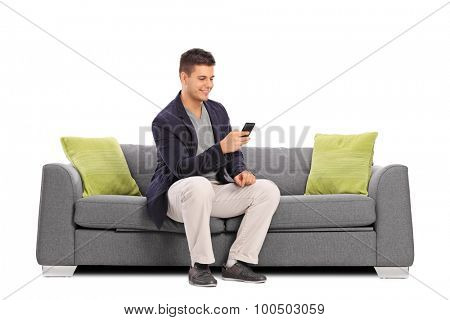 Cheerful young man sitting on a gray sofa and typing on his cell phone isolated on white background