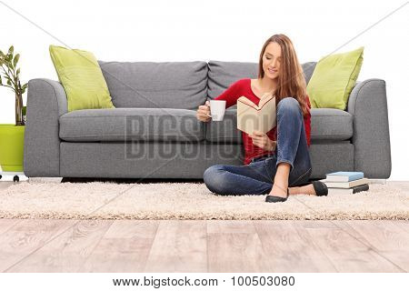 Relaxed young woman enjoying her morning coffee seated on the floor in front of a gray sofa and reading a book isolated on white background