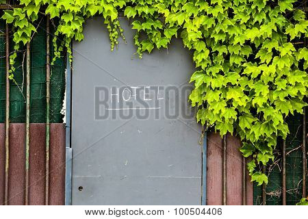 Hotel Entrance Door With Sign In A Fence With Green Foliage