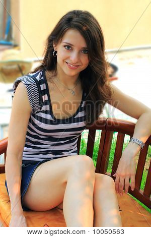 The young woman is sitting on the bench