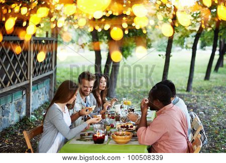 Group of young friends having traditional dinner on Thanksgiving Day