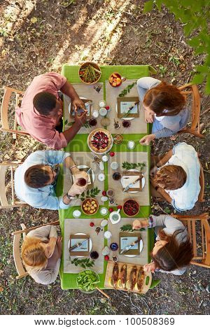 Young friends having dinner on Thanksgiving Day outdoors