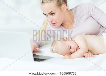 Sleeping baby next to mother using laptop