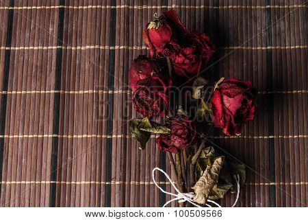 red dried rose bouquet being tied with rope