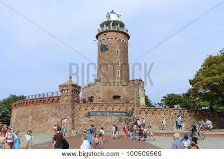 KOLOBRZEG - AUGUST 12: The area harbor and the lighthouse full of tourists who are watching the city's attractions on 12 August 2015 in Kolobrzeg, Poland. Visible lighthouse was built in 1945.