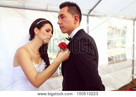 Bride Putting Rose Corsage On Groom's Chest
