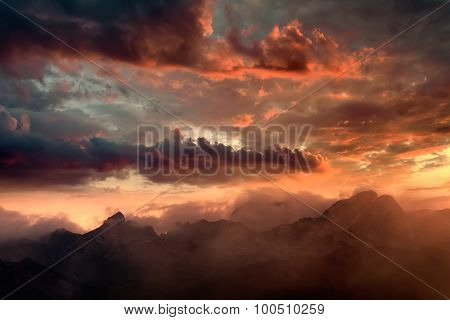 Fiery Sunset And Hazy Mountain Peaks