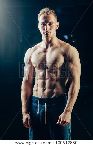 Silhouette of a athlete. Confident young fitness man with strong hands. Dramatic light.