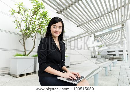 Businesswoman using the laptop computer at outdoor