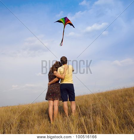 Happy young couple in love with flying a kite at countryside