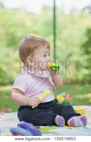 Baby, less than a year old   playing with  toy banana