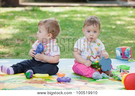 Babys, less than a year old, playing with  toys