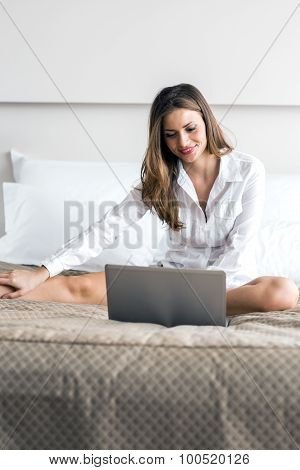 Beautiful Woman With Sexy Long Legs In Shirt Using A Notebook In Bed