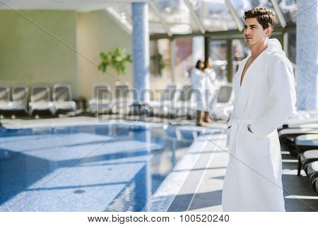 Man Standing Next To A Pool In A  Robe