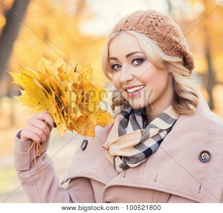 Attractive young woman being happy with a bouquet of leaves.