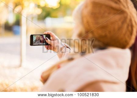Two girls taking selfies in the autumn park.
