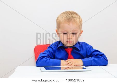 little boy wearing the tie and looking at touch pad
