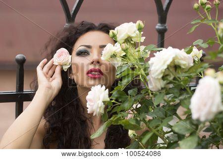 Glamour Young Woman Posing Near Rose Bush