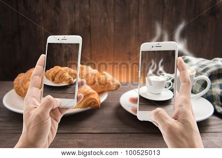 Taking Photo Of Coffee Cup And Croissant On Wooden Background