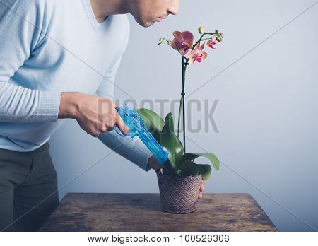 Man Watering Orchid With Water Pistol