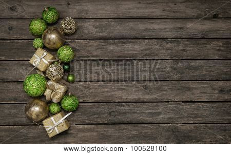 Old wooden background with christmas decoration in apple green and golden balls.