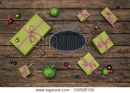 Old wooden dark brown background with apple green red white checked gift boxes for christmas.