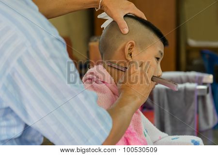 Young Asia boy getting his head shaved