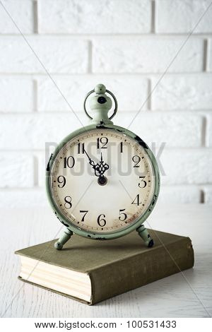 Clock and vintage book, on light wall background