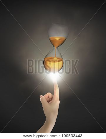 Human Finger Pointing At Hourglass With Bright Light