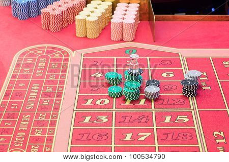 Casino American Roulette gambling table with a playing chips on the layout