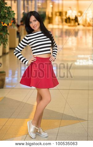 girl in a striped blouse walks around the store.
