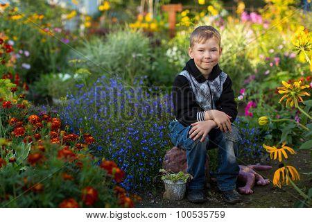 Cute little boy is sitting in the flower garden.
