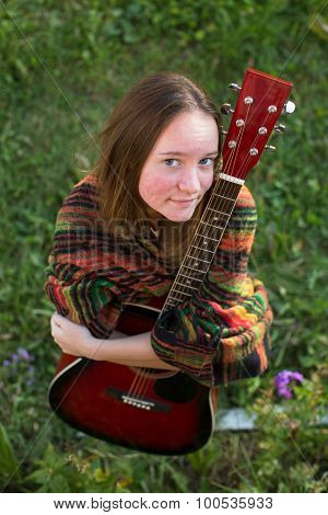 Young girl with acoustic guitar outdoors, portrait of a top view.