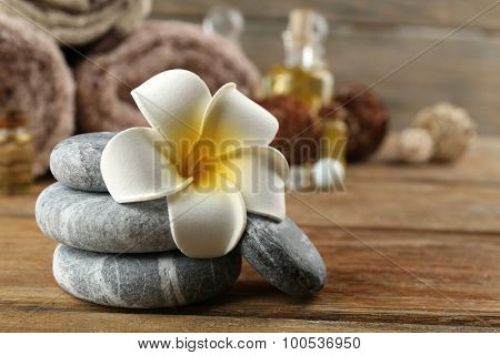 Stack of spa stones  and spa treatment on wooden background