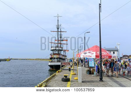 KOLOBRZEG - AUGUST 12: Tourists enjoy the sunny weather and walking on the harbor on 12 August 2015 in Kolobrzeg, Poland.