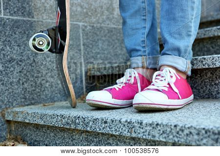 Young skateboarder in gumshoes and skate