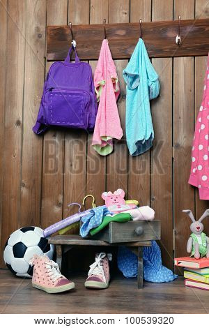 Children things hanging on wall and stacked in room