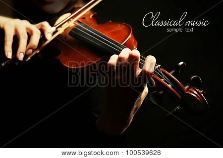 Violinist playing violin on dark background