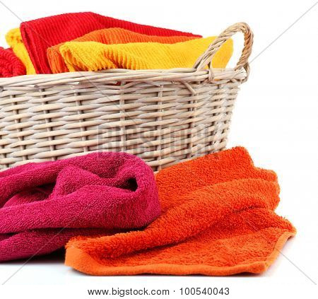 Colorful towels in basket isolated on white