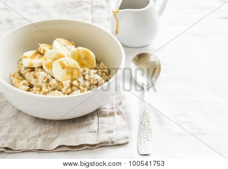 Oatmeal With Banana, Caramel Sauce  In A White Bowl On A Light Surface, A Delicious And Healthy Brea