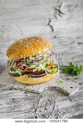 Delicious Veggie Burger With Cabbage, Tomato, Cucumber, Onions And Peppers On A Light Wooden Surface