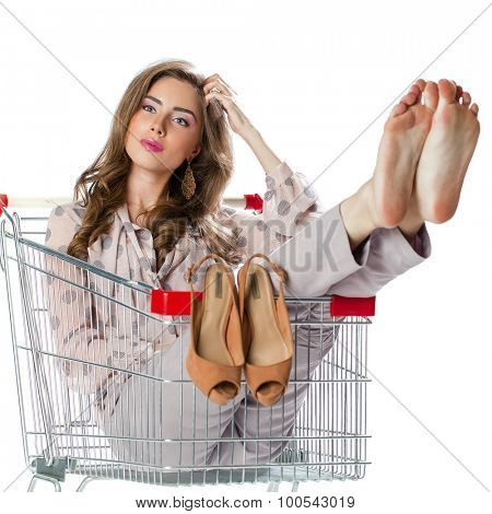 Young beautiful brunette girl sitting in an empty shopping trolley, isolated on white background