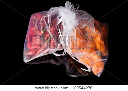 Two sacks with orange and red peppers