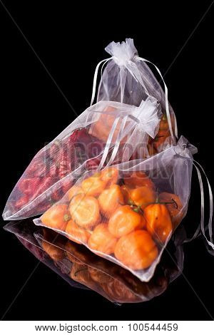 Three sacks with orange and red peppers