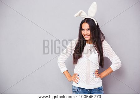 Portrait of a cheerful woman in bunny ears standing on gray background