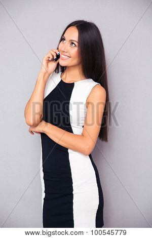 Portrait of a smiling beautiful woman talking on the phone and looking up over gray background