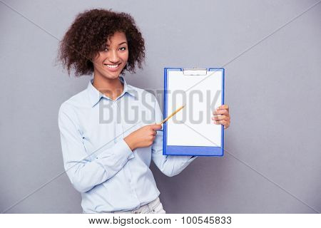 Smiling afro american woman showing blank clipboard over gray background